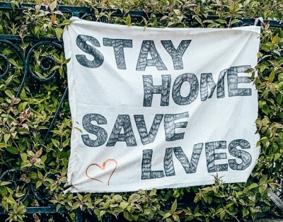 stay home save lives banner on fence